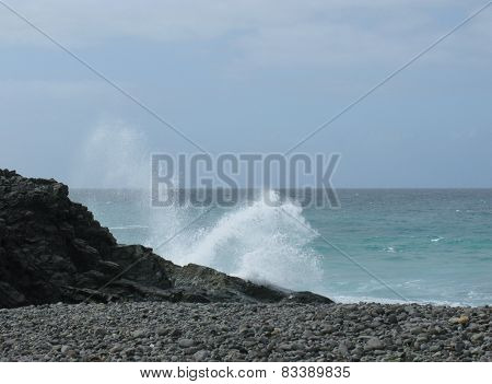 The ocean and a black pebble beach