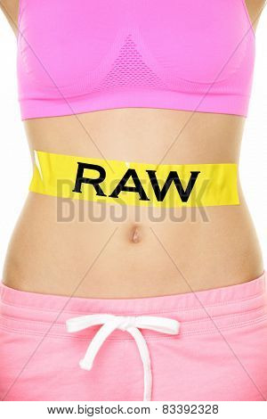 Raw food diet concept - closeup of woman's stomach eating only raw ingredients. New trend in nutrition of only uncooked or unprocessed food. Yellow label as warning or caution applied on body.