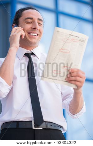 Smiling unemployed man in suit reading newpaper outdoors. poster