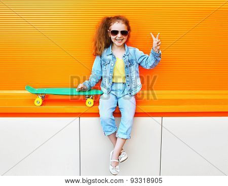 Fashion Kid. Stylish Little Girl Child Wearing A Jeans Clothes And Sunglasses With Skateboard Having