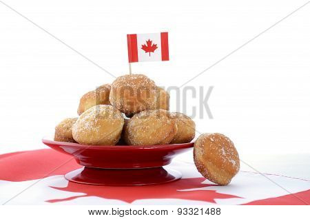 Stack of donut holes on red plate on Canadian maple leaf flag for Happy Canada Day celebration party. poster