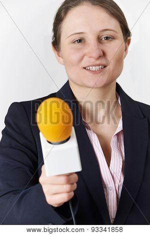 Studio Portrait Of Female Journalist With Microphone