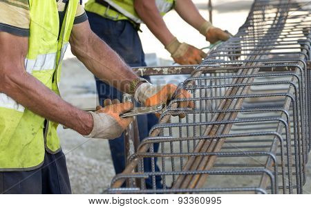 Close up of construction worker hands working with pincers on fixing steel rebar at building site poster
