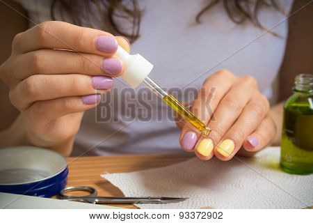 Female Hand Holding A Pipette With Oil