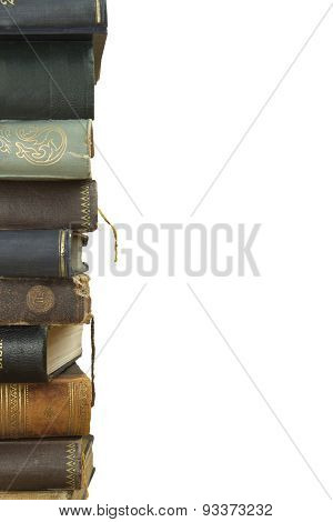 Front view of old books stacked on a shelf.