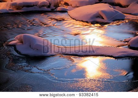 Snake like snow figure in the middle of the icy river