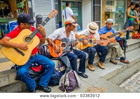 Unidentify indigenous men playing guitar in the commercial street plaza of Armenia, Colombia