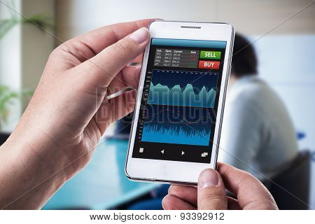 a woman holding a smart phone running a trading or forex app with charts and data poster