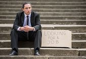 Man in suit sitting at stairs with sign. Unemployed man looking for job. poster
