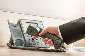 Closeup of a hand in a formal elegant suit dialing a telephone number on a classical black landline phone. Conceptual of global business communication and telemarketing. poster