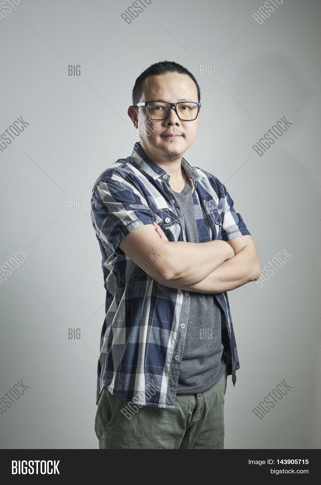 362ba5efc Portrait of happy single mature 40s Asian man in casual arms crossed  smiling and standing over