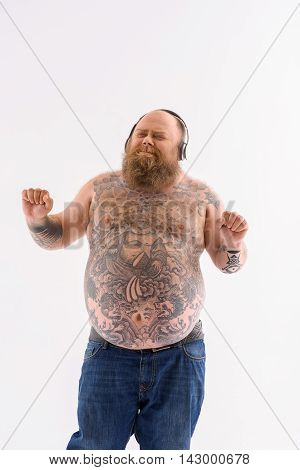 Joyful fat man is listening to music from headphones. He is standing and dancing. His eyes are closed with pleasure. Isolated