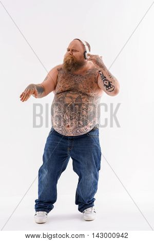 Cool fat man is listening to music with pleasure. He is touching headphones and dancing. Isolated