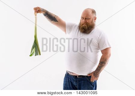 What it this. Thick man is holding leek and looking at it with disgust. He is standing and putting hand in pocket. Isolated