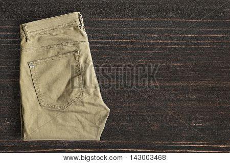 Folded khaki pants on dark wooden background