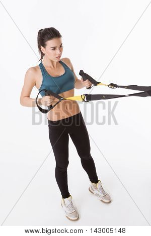 Top view of pretty lady posing with suspension trainer sling or suspension straps in studio. Upper body excercise concept. Lady exercising on TRX.