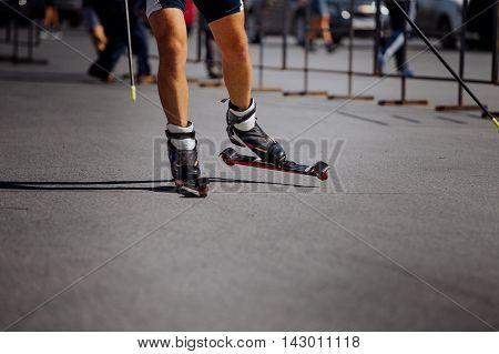 feet male athlete in ski-roller rides on asphalt