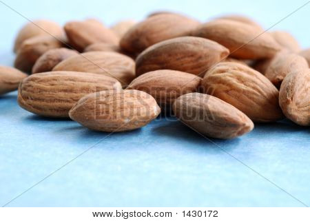 A Pile Of Almonds Against A Blue Background 3