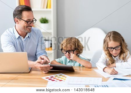 Everyone is busy. Pensive girl drawing while cheerful man showing something to a surprised little boy while sitting at the table