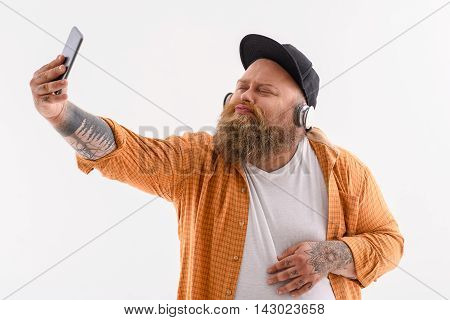 Cheerful fat hipster is making selfie on mobile phone. He is sending air kiss to camera with joy. Man is standing and listening to music from headphones. Isolated