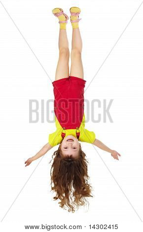 Cheerful Little Girl Hangs Upside Down On White