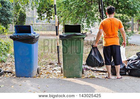 Man carrying garbage bag near wheel bins at dump