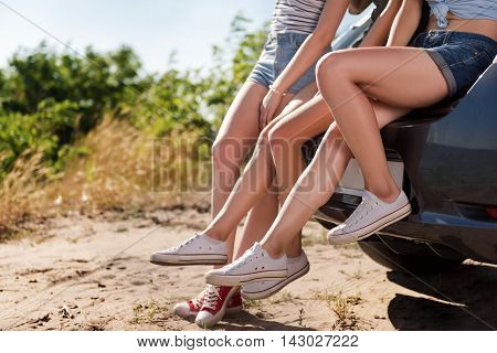 Active way of life. Pleasant young girls standing near the car while resting outdoors