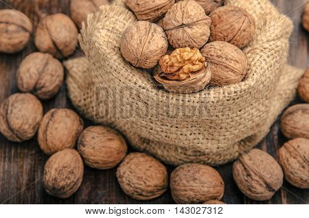 Pile of walnuts in shellin a bag on a wooden background . Linen sack with walnuts in the background. toning