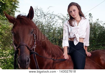 Beautiful young woman riding a chestnut horse