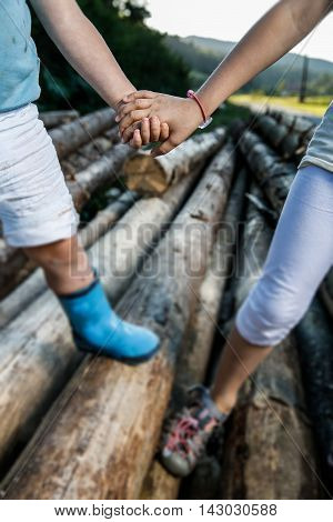 Friends holding hands enjoying their time together. Happy carefree outdoor countryside childhood siblings love and companionship family values concept.