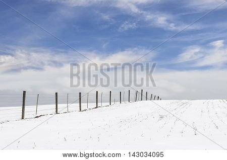 Fence in Snow Covered Field with Clouds and Blue Sky