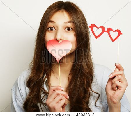 Party image. Playful young woman holding a party heart.