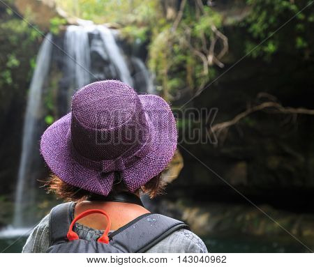 Woman with purple hat seen from behind looking at a water fall