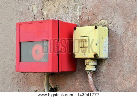 emergency switch and light switch on the wall of a factory building