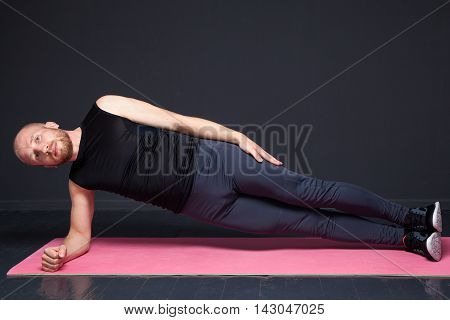 Young fitness man performing side plank on the mat