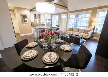 Modern round dining room table set for dinner in a luxury house with a kitchen in the background. Interior design.