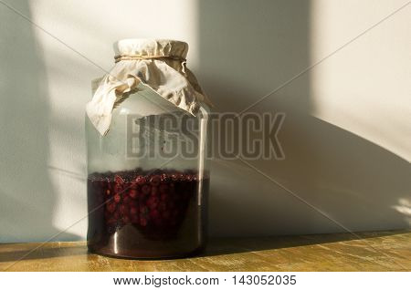 Large glass jar with sugar soaked sour cherries for making homemade liqueur