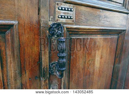 An antique wooden door with code-lock and an old door handle