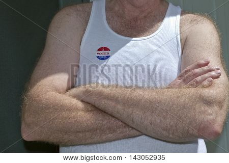 Asheville, North Carolina, USA - August 5, 2012: Close up of an older white American man with his arms crossed wearing a white undershirt and a