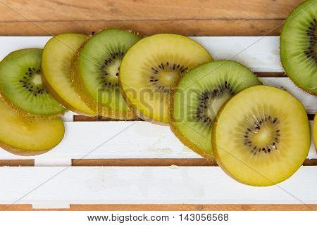 Kiwi.Yellow kiwi and green kiwi fruit isolated on wooden background