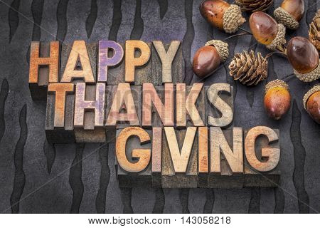 Happy Thanksgiving greeting card - word abstract in vintage letterpress wood type with acorn and cones fall decoration against lokta paper