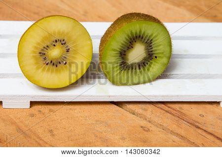 Kiwi sliced. Yellow kiwi and green kiwi fruit isolated on wooden background