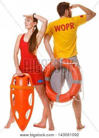Lifeguards with rescue tube and ring buoy lifebuoy. Man and woman supervising swimming pool looking out into the distance. Accident prevention.