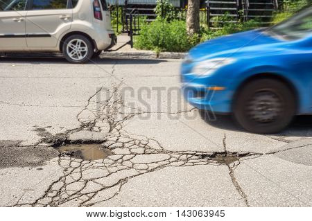 Large deep pothole with car approaching in Montreal street Canada.