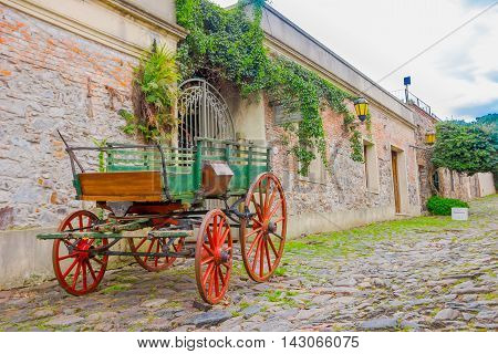 COLONIA DEL SACRAMENTO, URUGUAY - MAY 04, 2016: ancient cart parked in the street next to an old house entrance.