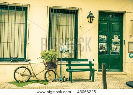 COLONIA DEL SACRAMENTO, URUGUAY - MAY 04, 2016: abandoned bicycle with a tree on the basket parked outside a house next to a bench.