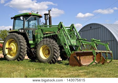 WATFORD, NORTH DAKOTA, June 26, 2016: The John Deere 740 tractor and front end hay loader are products of John Deere Co, an American corporation that manufactures agricultural, construction, forestry machinery, diesel engines, and drivetrains.