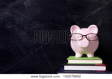 Piggybank with glasses and blackboard copy space