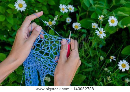 Female Hands Crochet Blue Cotton Yarn Openwork Fabric On A Background Of Green Grass