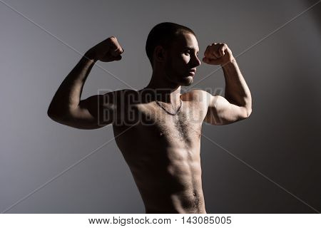The athlete demonstrates muscles. A young man with a naked torso standing in the studio on a gray background.